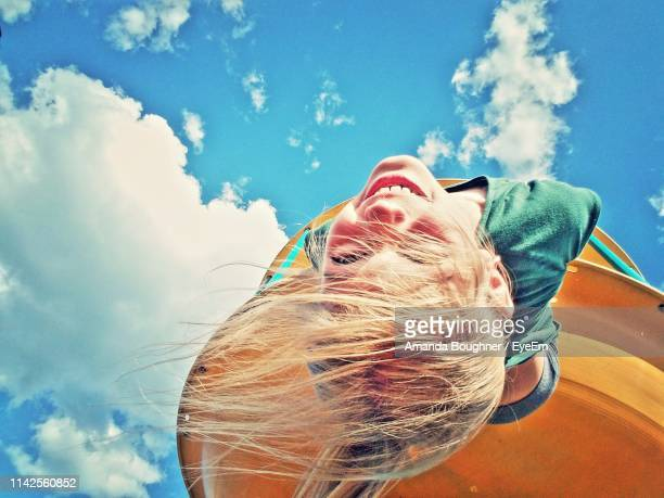 low angle portrait of girl hanging against sky - innocenza foto e immagini stock