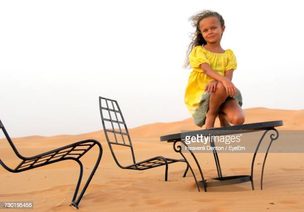 Low Angle Portrait Of Girl Sitting On Abandoned Table In Sahara Desert Against Clear Sky