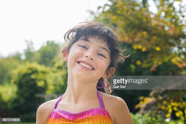 Low angle portrait of girl wearing colourful halter top looking at camera smiling