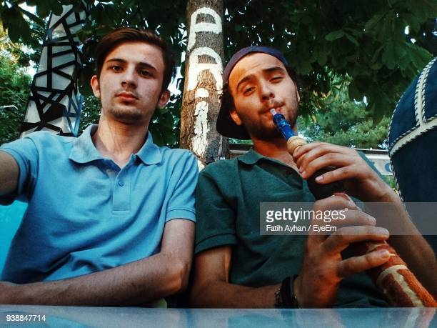 low angle portrait of male friends sitting at table against tree - 水キセル ストックフォトと画像
