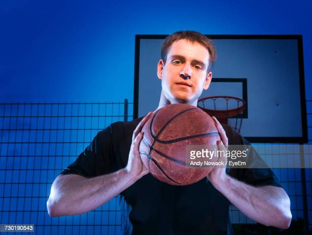 Low Angle Portrait Of Man Holding Basketball Against Blue Sky