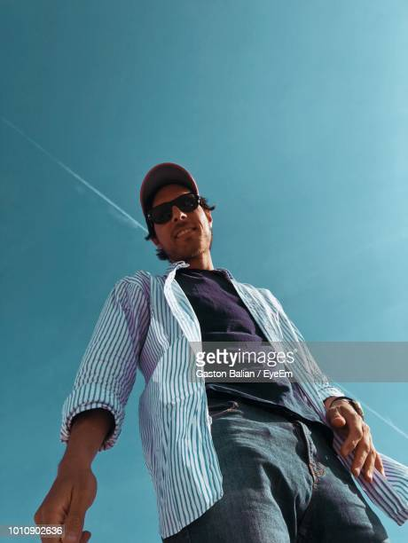 low angle portrait of man in sunglasses standing against blue sky - vista de ángulo bajo fotografías e imágenes de stock