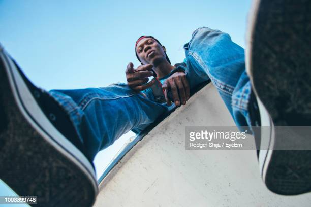 low angle portrait of man sitting on retaining wall against clear sky - low angle view stock pictures, royalty-free photos & images