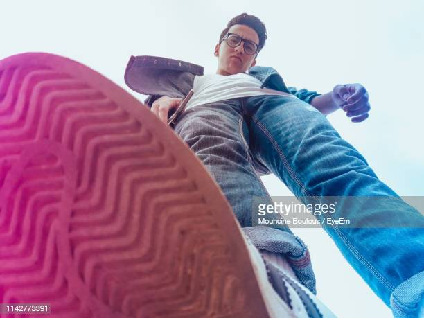low angle portrait of man standing against sky - low angle view stock pictures, royalty-free photos & images