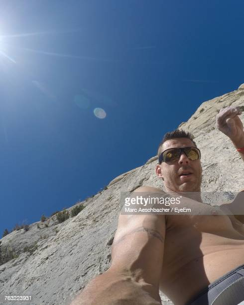 Low Angle Portrait Of Mature Man Standing By Rock Formation Against Clear Blue Sky