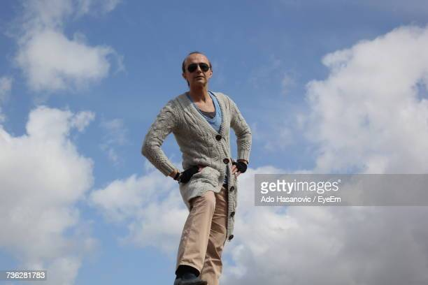 Low Angle Portrait Of Mature Man With Hands On Hip Standing Against Cloudy Sky