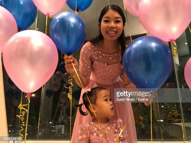 low angle portrait of mother with daughter amidst balloons during birthday - pink dress stock pictures, royalty-free photos & images