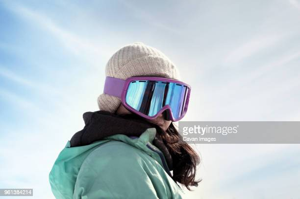Low angle portrait of skier against sky