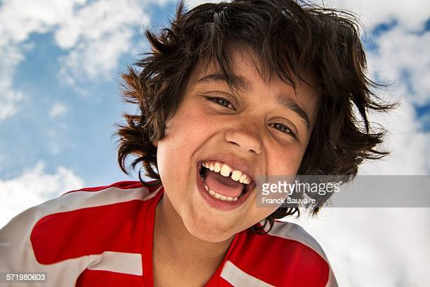 Low angle portrait of smiling boy in front of sky