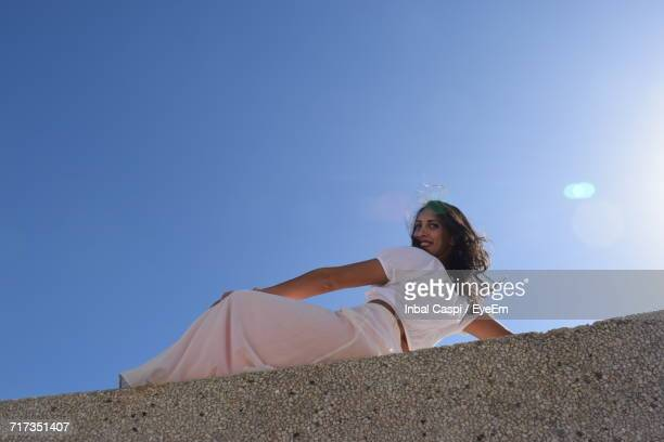 Low Angle Portrait Of Smiling Woman Reclining On Retaining Wall Against Clear Blue Sky