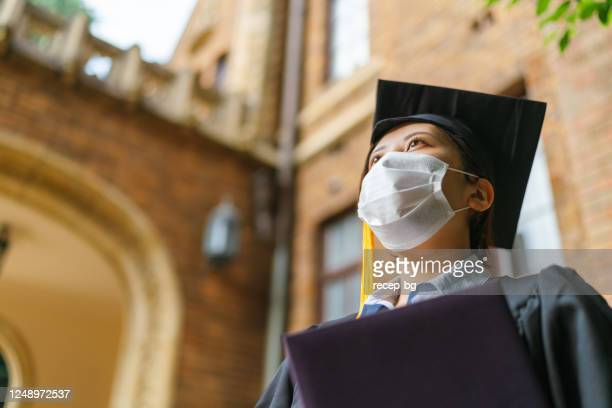 low angle portrait of student in graduate gown with diploma - ceremony stock pictures, royalty-free photos & images