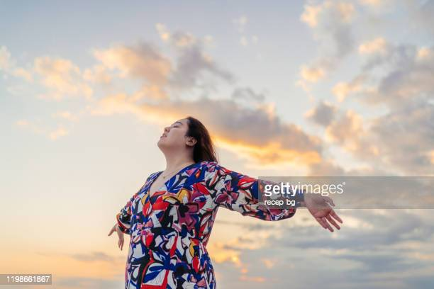 low angle portrait of woman outstretching her arms - plus size model stock pictures, royalty-free photos & images