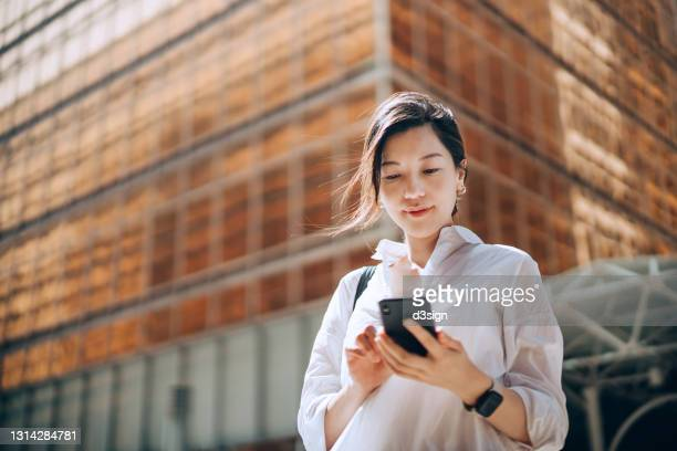 low angle portrait of young asian businesswoman checking emails on smartphone outside office building in financial district. with contemporary corporate skyscrapers in background. making business connections throughout the city - hong kong stock pictures, royalty-free photos & images