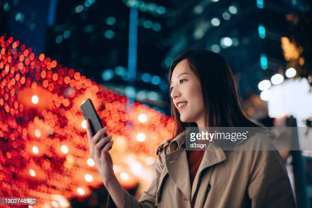 low angle portrait of young asian businesswoman using smartphone in the city at night, against illuminated urban commercial buildings and vibrant city street lights. business on the go - hong kong stock pictures, royalty-free photos & images