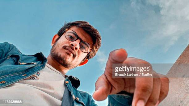 low angle portrait of young man against sky - low angle view stock pictures, royalty-free photos & images