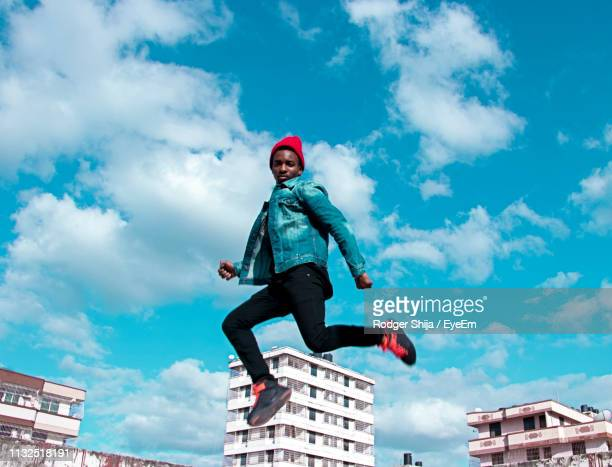low angle portrait of young man jumping against blue sky - secteur de la mode photos et images de collection