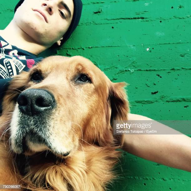 low angle portrait of young man with golden retriever by green wall - seeing eye dog stock photos and pictures