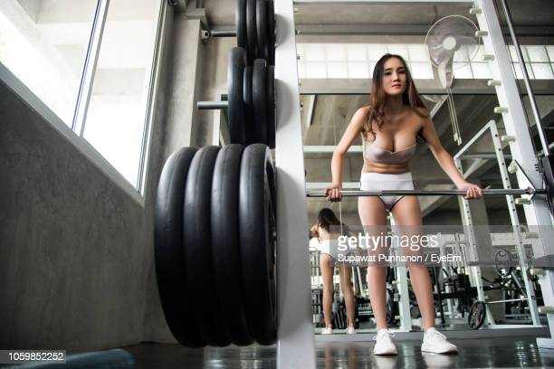 low angle portrait of young woman exercising in gym - off shoulder stock pictures, royalty-free photos & images