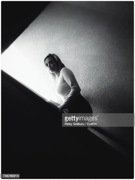 Low Angle Portrait Of Young Woman Moving Up On Steps Of Building