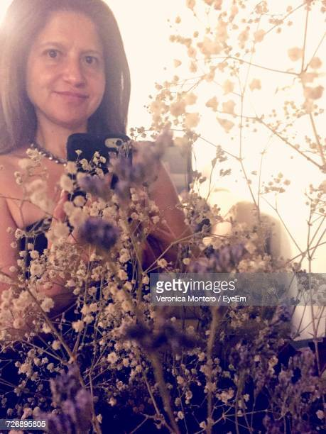 low angle portrait of young woman using mobile phone by wildflowers blooming outdoors - montero flor fotografías e imágenes de stock
