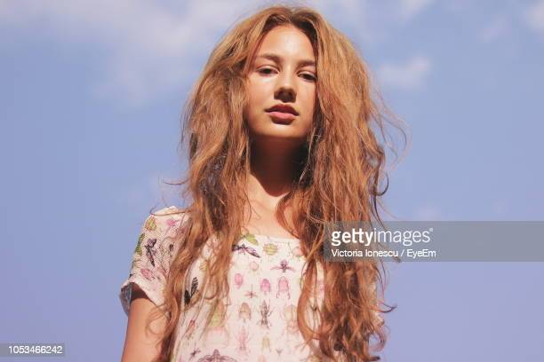 low angle portrait of young woman with messy hair against sky - frizzy stock pictures, royalty-free photos & images
