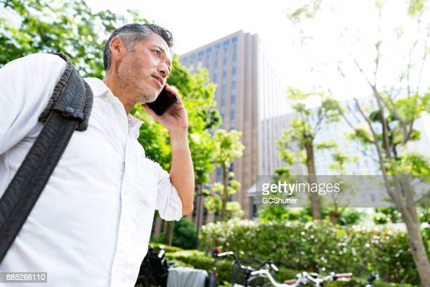 彼の携帯電話で話しながら通りを歩いていた年配の男性に将来ローアングル - もがく ストックフォトと画像