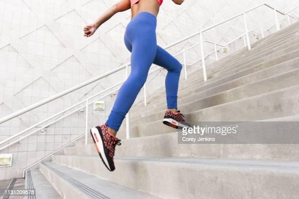low angle rear view of young woman, wearing sports clothing running up stairs - corredor caraterística de construção imagens e fotografias de stock