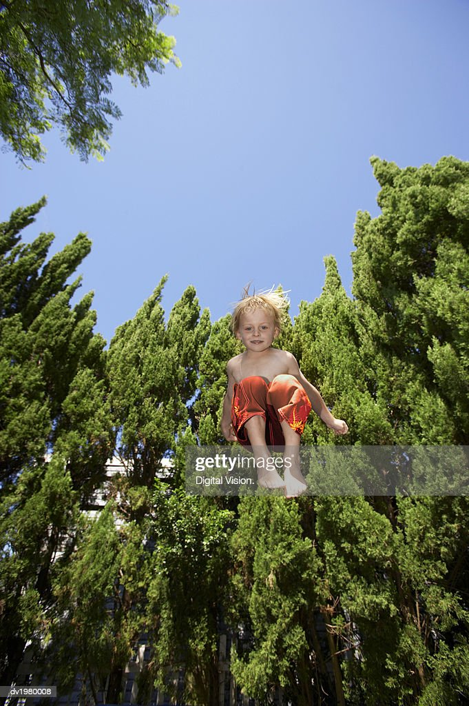 Low Angle Shot of a Boy Jumping in Mid Air : Stock Photo