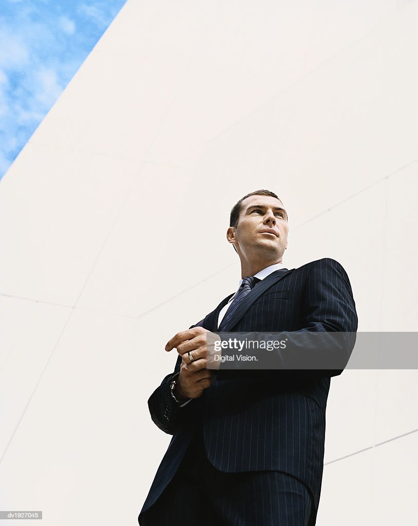 Low Angle Shot of a Businessman Standing by a Building : Stock Photo
