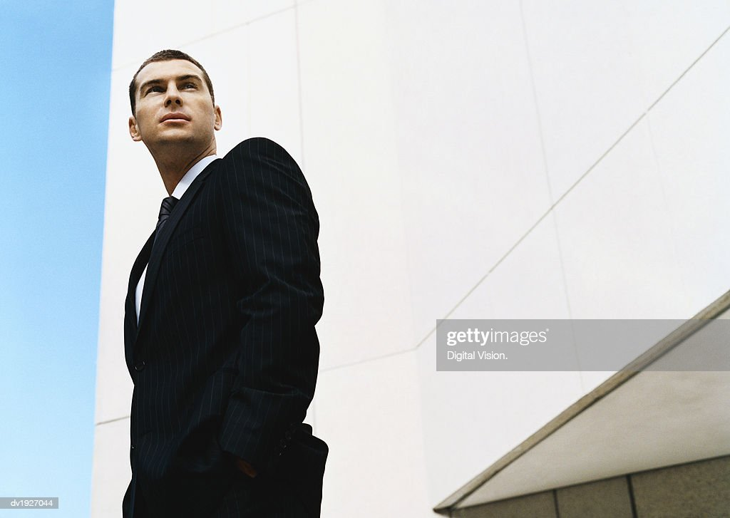 Low Angle Shot of a Businessman Standing by a Building With His Hands in His Pockets : Stock Photo