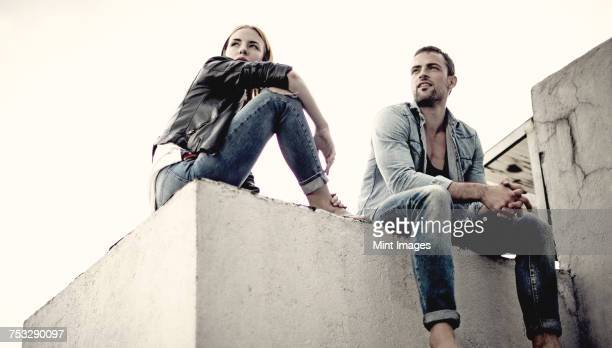 A low angle shot of a couple sitting on a city rooftop.