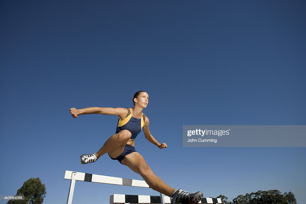 Low Angle Shot of a Determined Female Athlete Jumping Over a Hurdle : Stock Photo