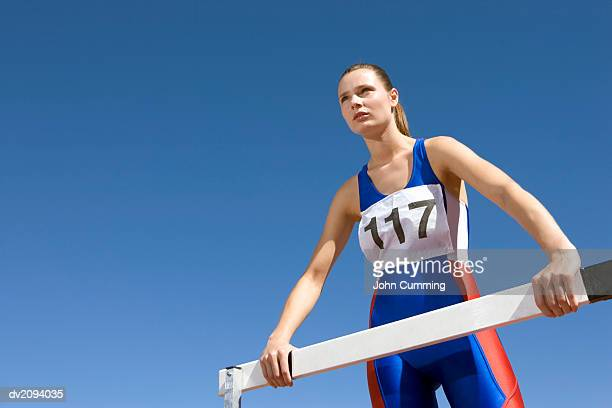 Low Angle Shot of a Determined Female Athlete Standing by a Hurdle