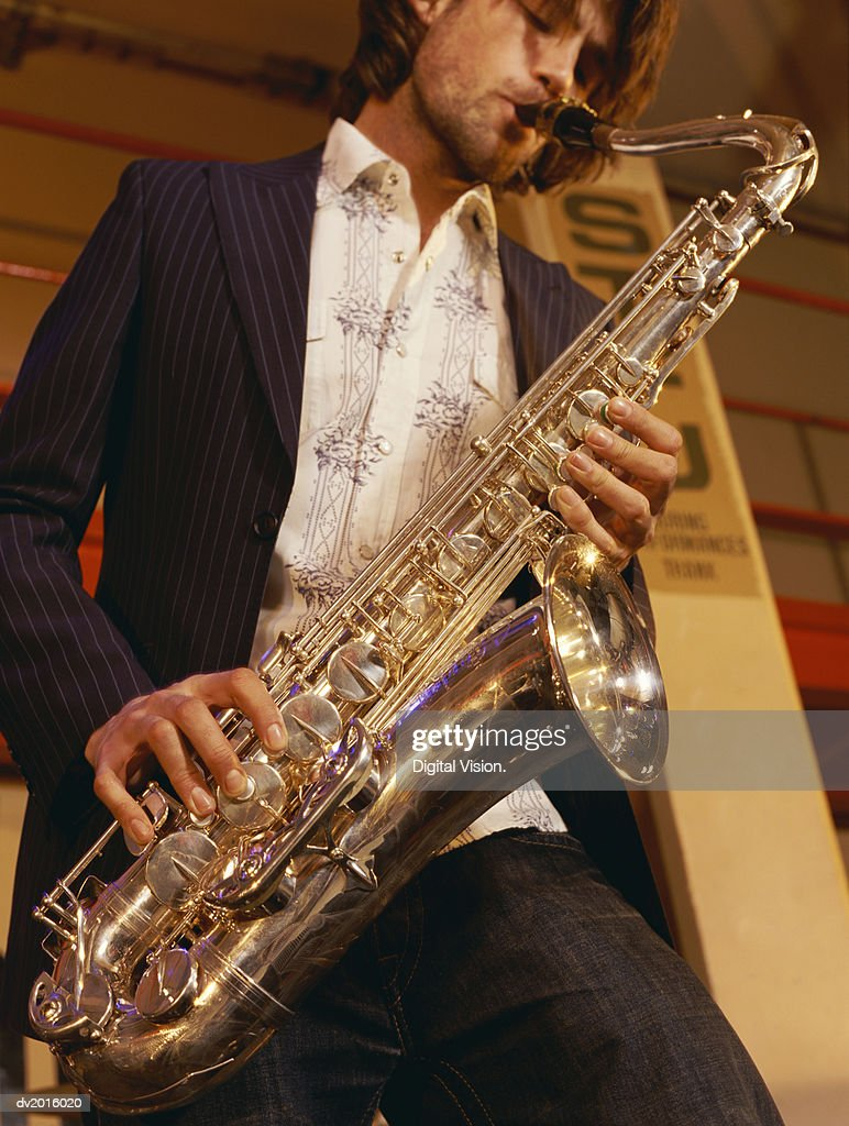 Low Angle Shot of a Man Playing a Saxophone : Stock Photo