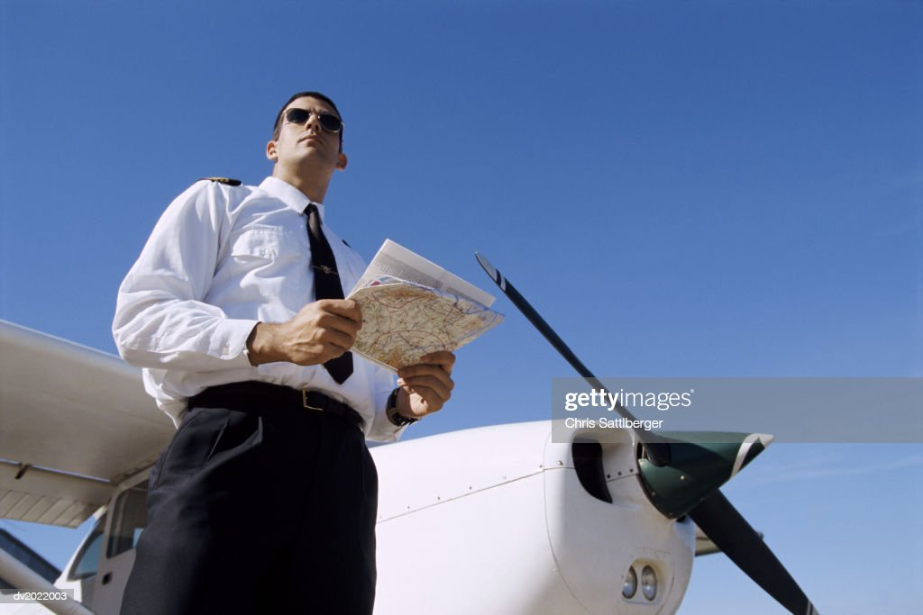 Low Angle Shot of a Pilot Holding a Map and Standing by a Private Propeller Plane : Stock Photo