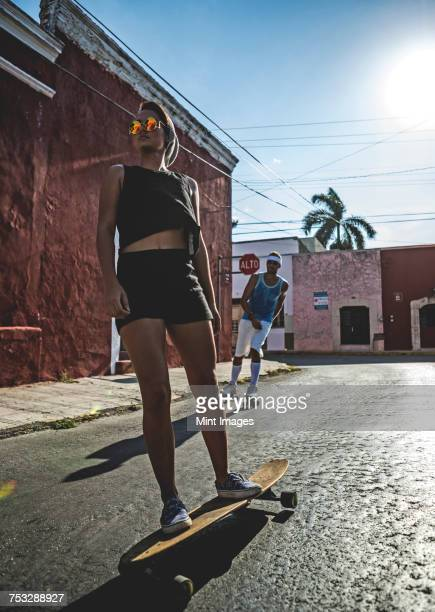 Low angle shot of a woman and man skateboarding and roller-skating down a street.
