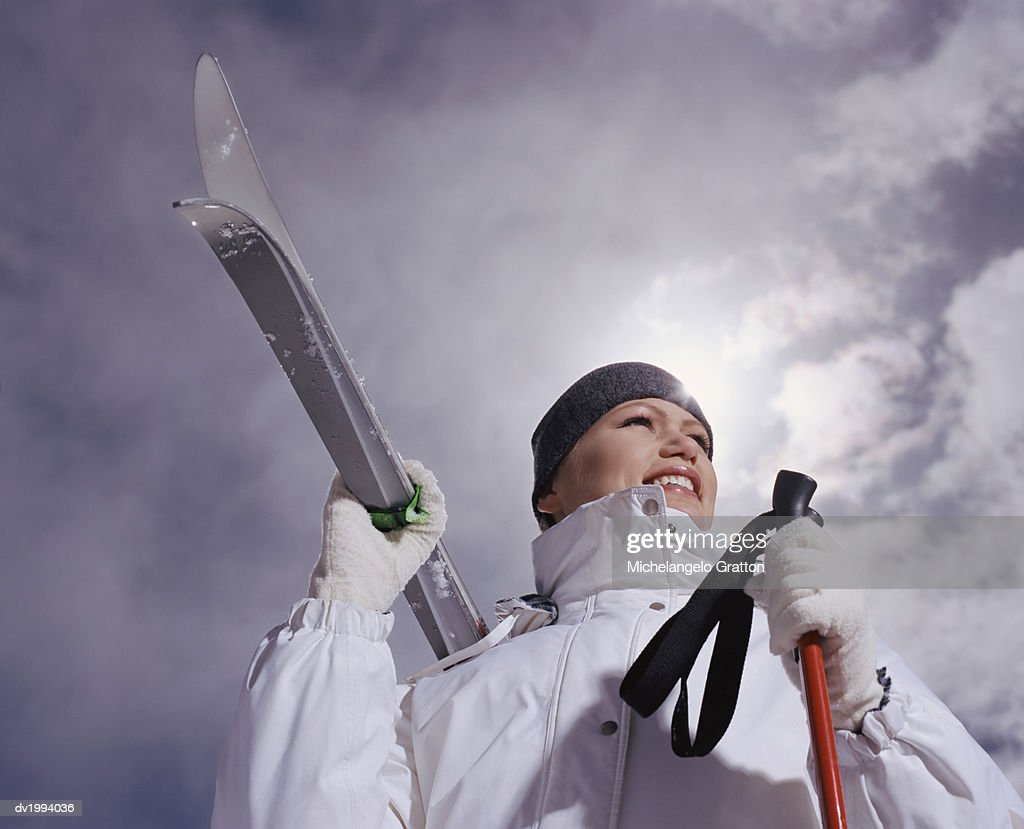 Low Angle Shot of a Young, Smiling Woman Holding Her Skis and Ski Poles : Stock Photo