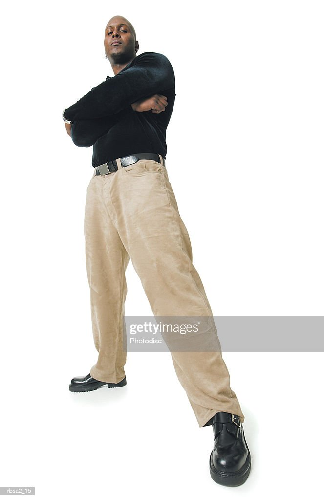 low angle shot of an african american man in tan pants and a black shirt as he folds his arms and smiles : Foto de stock