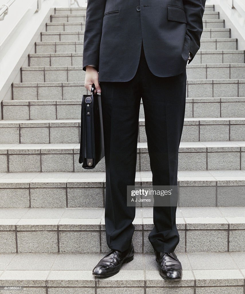 Low Angle Shot of an Unrecognizable Businessman Standing on Stone Steps and Holding a Briefcase : Stock Photo