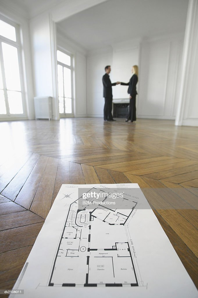 Low Angle Shot of Blueprints on a Wooden Floor in an Empty Room, with a Businessman Shaking Hands with a Businesswoman in the Background : Stock Photo