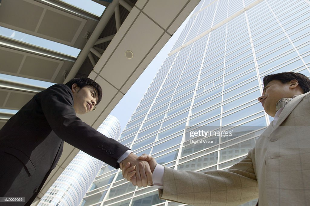 Low Angle Shot of Businessmen Shaking Hands : Stock Photo