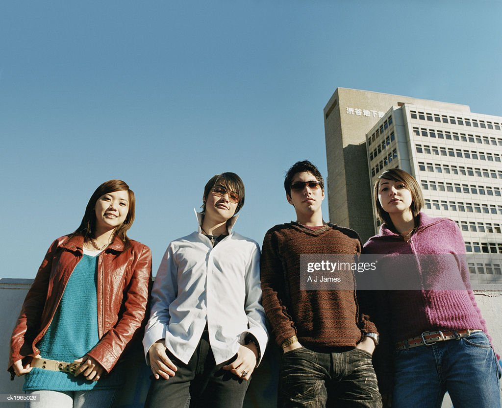 Low Angle Shot of Four Young Friends Leaning Against a Wall : Stock Photo