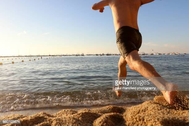 low angle shot of man running into sea - striding stock pictures, royalty-free photos & images