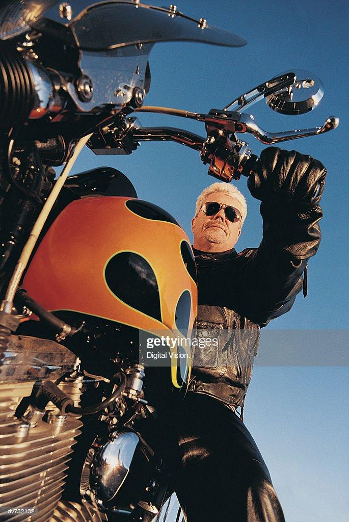 Low Angle Shot of Mature Man Riding a Motorbike : Stock Photo
