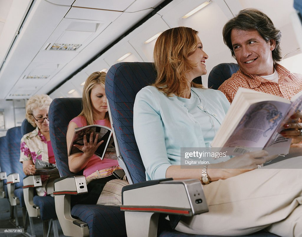 Low Angle Shot of Passengers Sitting on a Plane : Stock Photo