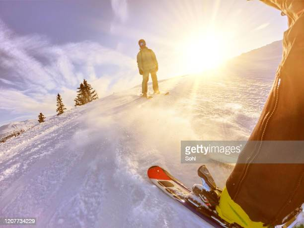 low angle shot of skier running down hill - alpine skiing stock pictures, royalty-free photos & images