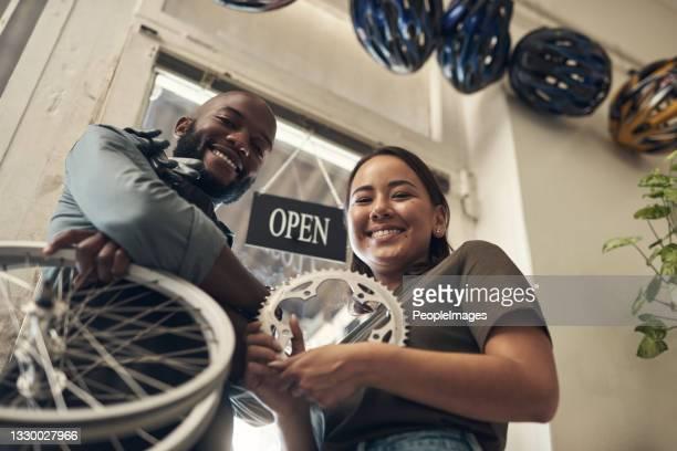 自転車店で一緒に立ち、スペアパーツを持っている2人の若いビジネスオーナーのローアングルショット - クランクセット ストックフォトと画像