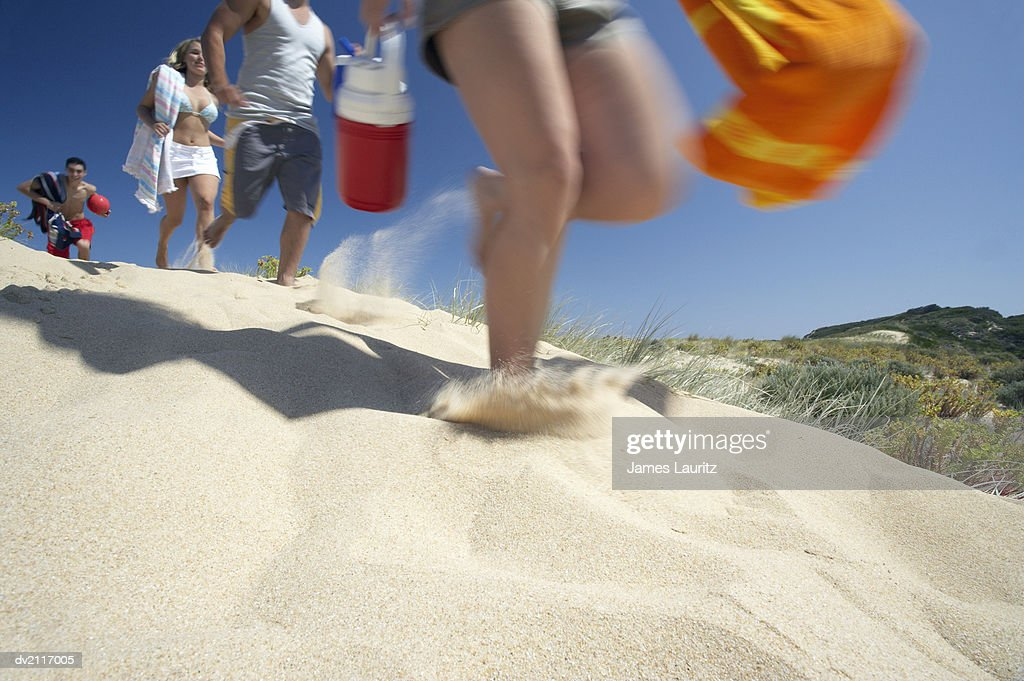 Low Angle Shot of Young People Running Across a Beach : Stock Photo