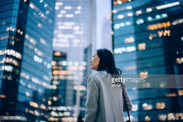low angle side profile of confident and professional young asian businesswoman looking up while standing against contemporary corporate skyscrapers with illuminated facade in financial district in the evening. female leadership and determined to success - business stock pictures, royalty-free photos & images