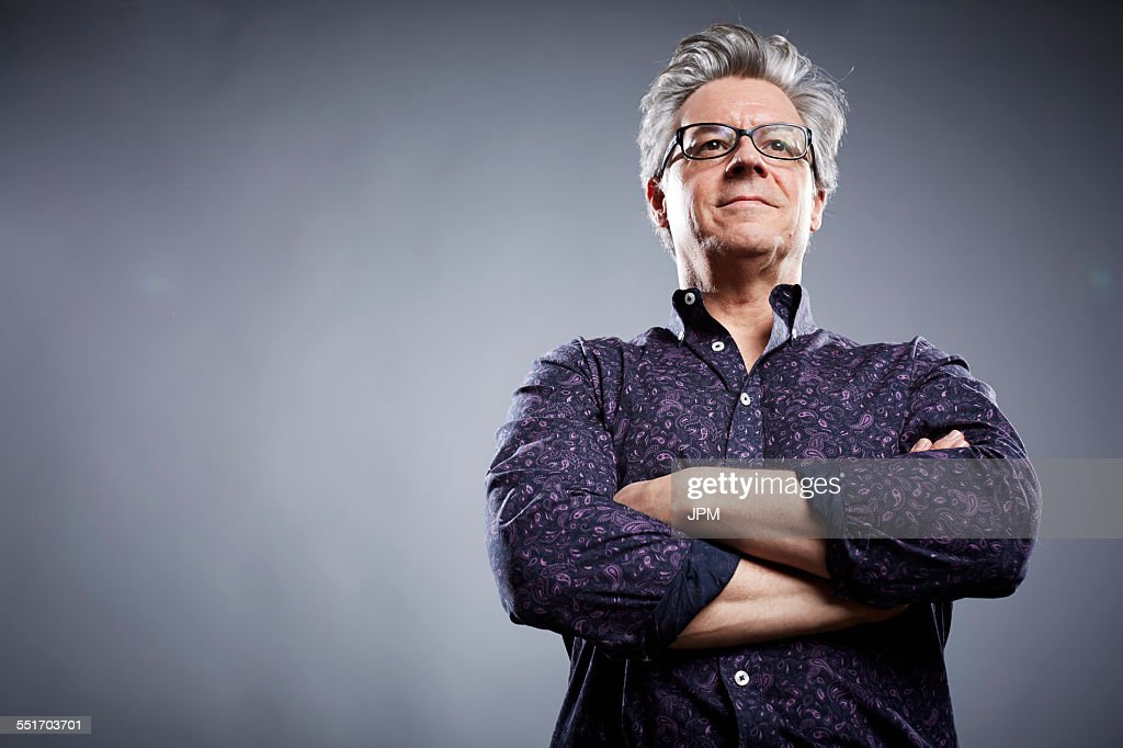 Low angle studio portrait of mature businessman with arms folded : Stock-Foto